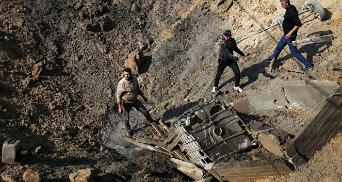 فلسطينيون يتفقدون موقع غارة جوية إسرائيلية على ميناء قيد الإنشاء في جنوب قطاع غزة