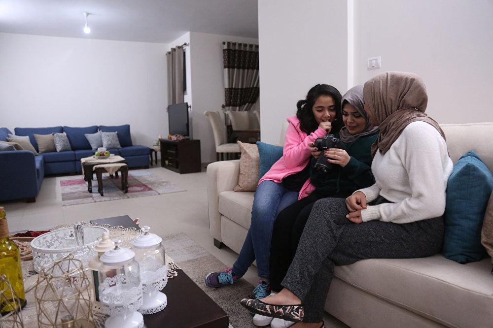 الشابة الفلسطينية ندى رضوان (وسط)، 27 عاما، خريجة كلية اللغة الإنجليزية، تشاهد فيديو مسجل لها من قبل أختها لمى رضوان (يمين)، 22 عاما، في منزلهن في مدينة غزة، 16 ديسمبر/ كانون الأول 2018