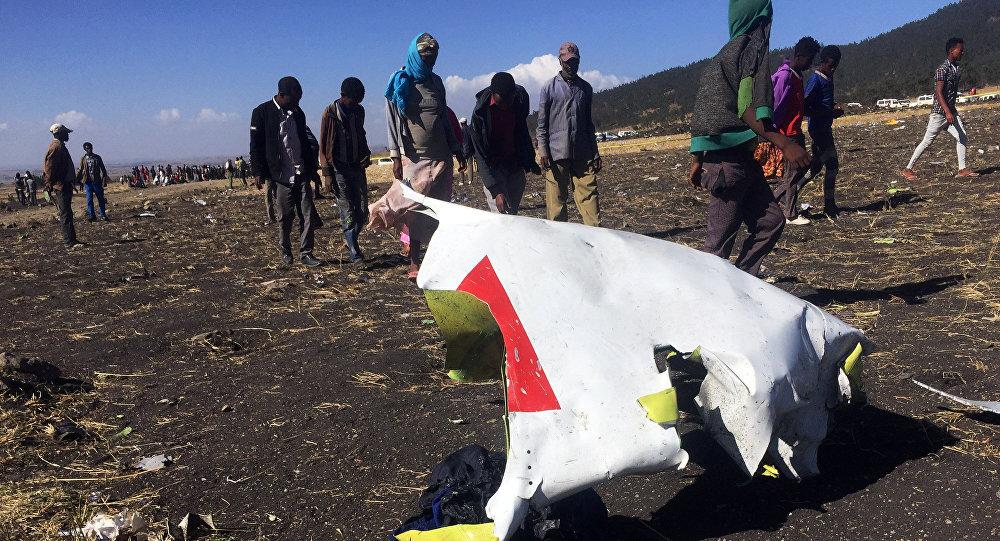 أشخاص يمشون بجوار جزء من الحطام في مكان تحطم طائرة الخطوط الجوية الإثيوبية بالقرب من مدينة بيشوفو جنوب شرق أديس أبابا