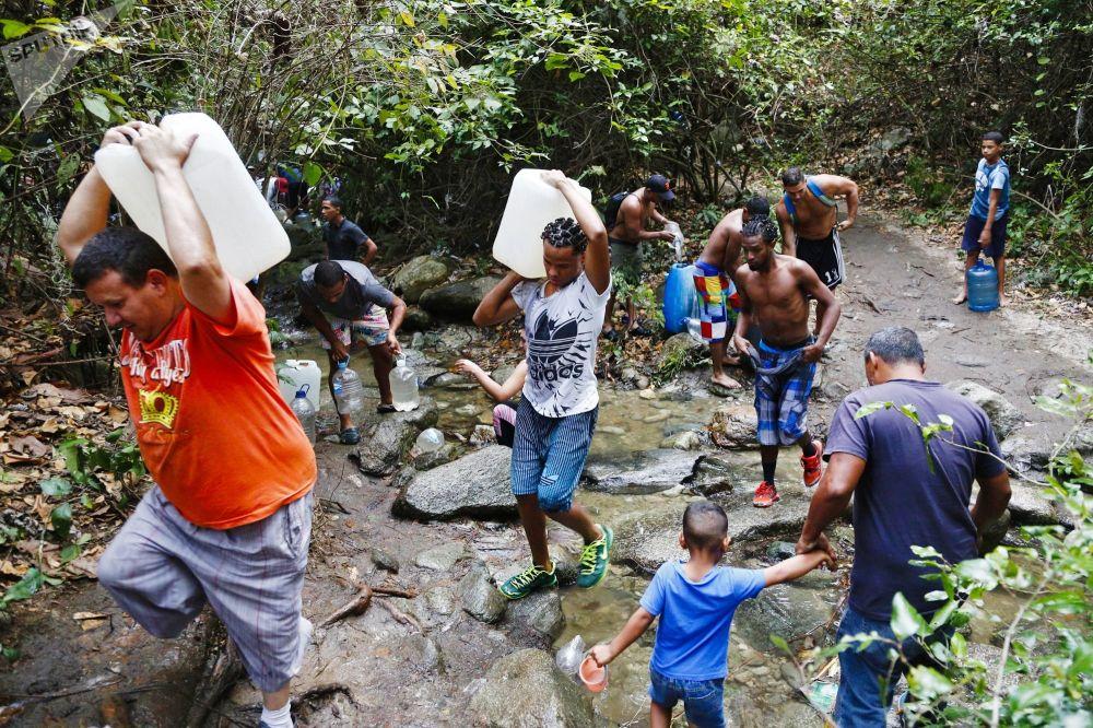 أشخاص يملأون العبوات والزجاجات بالمياه القادمة من جبل أفيلا إلى كراكاس