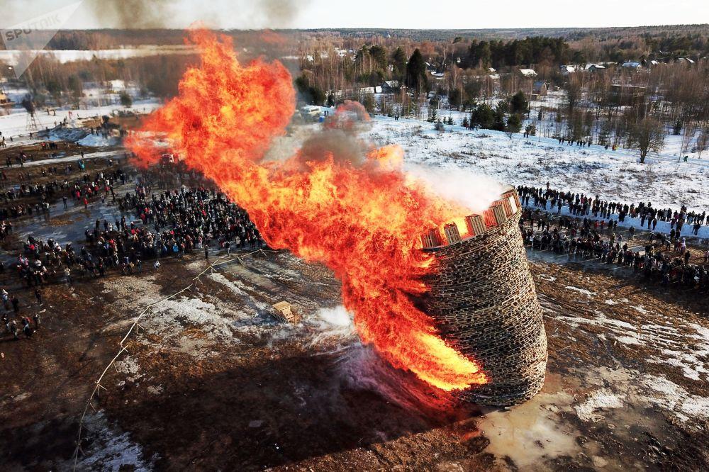 المشاركون في الاحتفال بمهرجان ماسلينيتسا (أسبوع المرافع)  أثناء حرق نموذج من القش في أراضي قرية نيكولا لينيفيتس الروسية