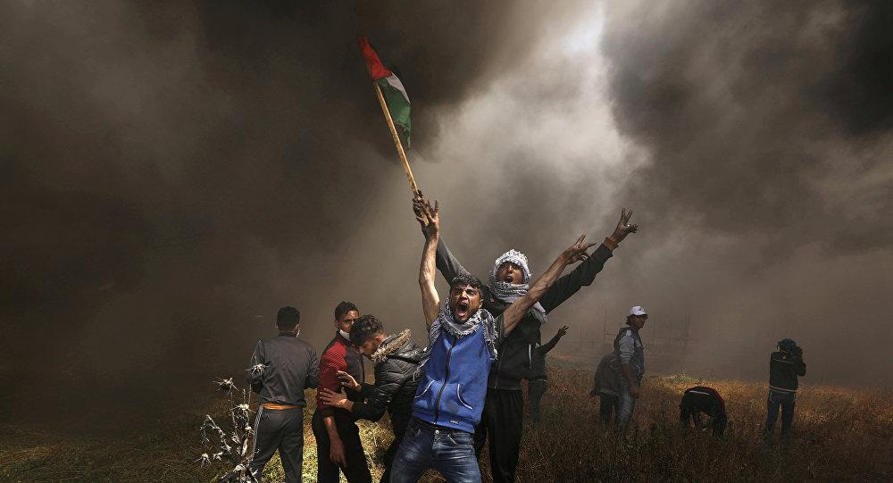 متظاهرون فلسطينيون يصرخون خلال اشتباكات مع القوات الإسرائيلية في احتجاج على الحدود بين إسرائيل وغزة شرق مدينة غزة
