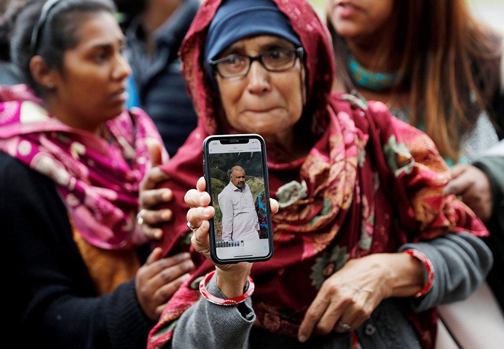 أكتر تحمل صورة لزوجها الذي تقول إنه مفقود بعد هجمات مسجد الجمعة خارج مركز اجتماعي بالقرب من مسجد النور في كرايستشيرش