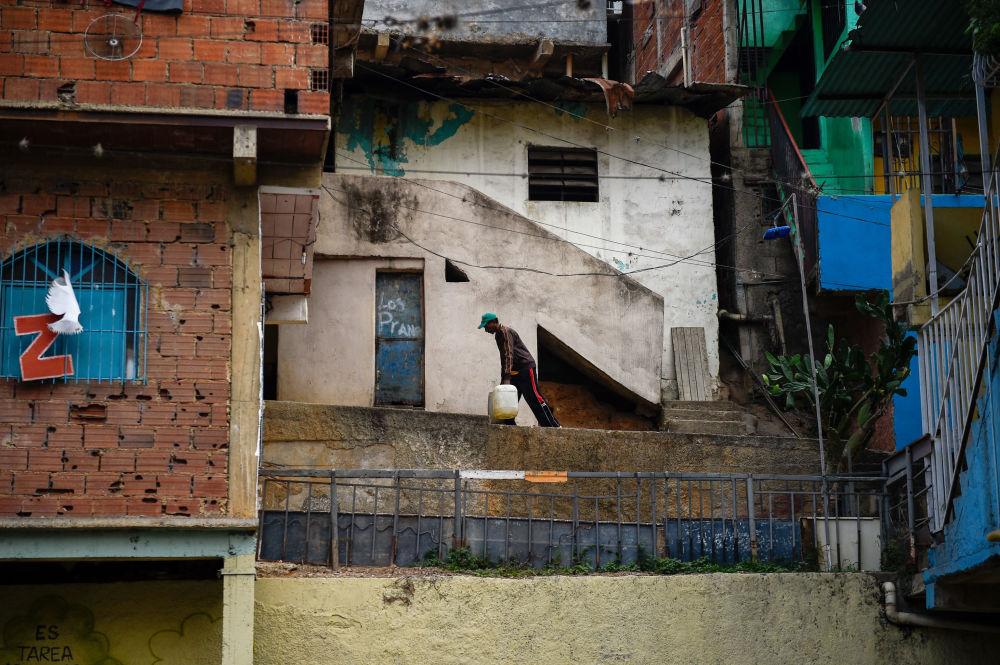 مواطن محلي يحمل وعائين من المياه، كاراكاس، فنزويلا، 1 أبريل/ نيسان 2019