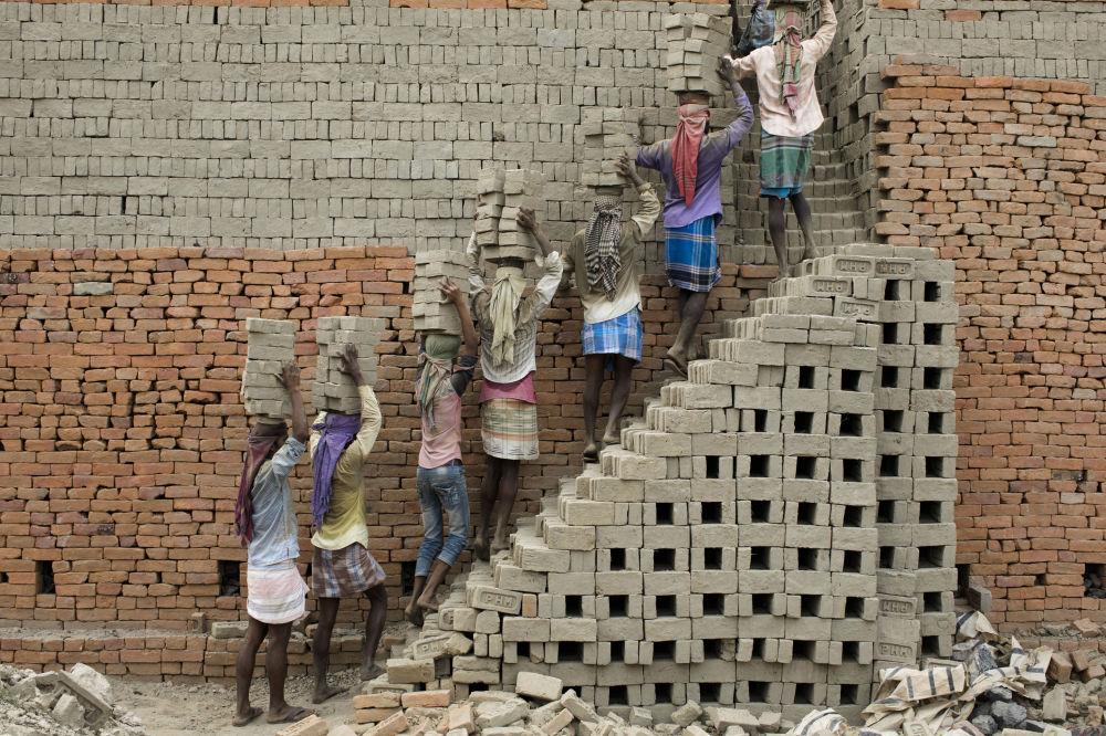 عمال يحملون طوبًا من الطين إلى الفرن، فاراكا، الهند 3 أبريل/ نيسان 2019
