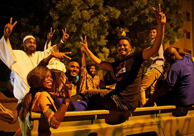 متظاهرون سودانيون يحتفلون بعد تنحي وزير الدفاع عوض بن عوف من رئاسة المجلس العسكري الحاكم في البلاد