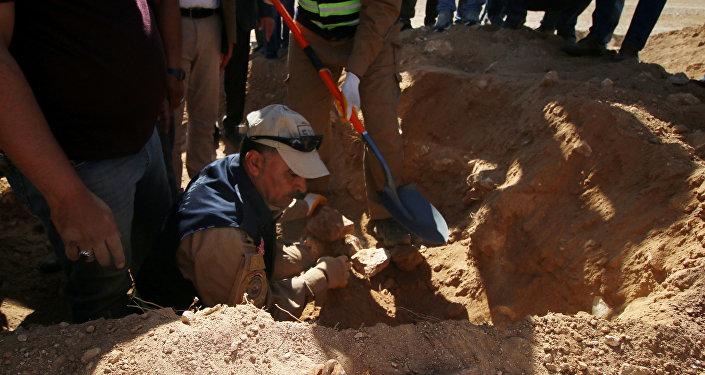عراقيون من الدفاع المدني وأكراد يفحصون مقبرة جماعية اكتشفت للأكراد في غرب مدينة السماوة