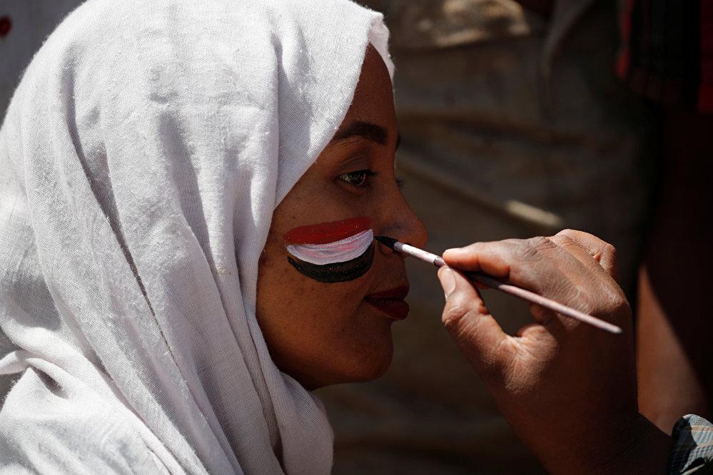رجل يرسم العلم السوداني على وجه المتظاهرين في الخرطوم