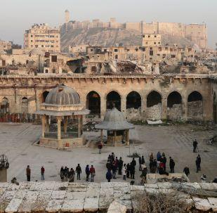 جامع حلب الكبير، على خلفية قلعة حلب (القرن الـ13)، في البلدة القديمة في حلب، عام 2017