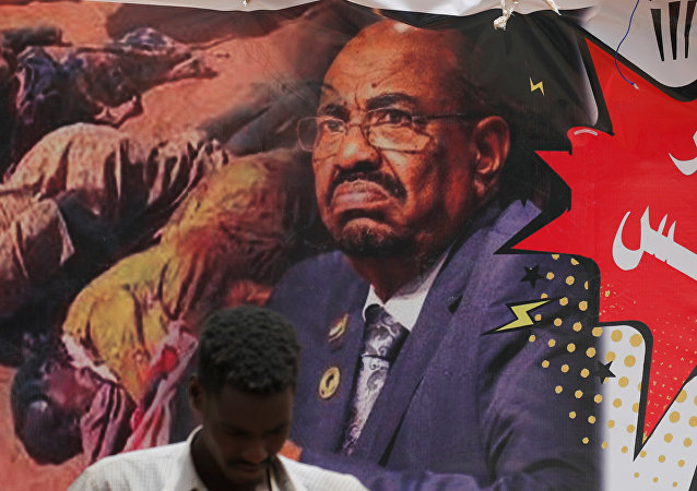 متظاهر يقف أمام لافتة تصور الرئيس السوداني السابق عمر البشير أمام وزارة الدفاع في الخرطوم