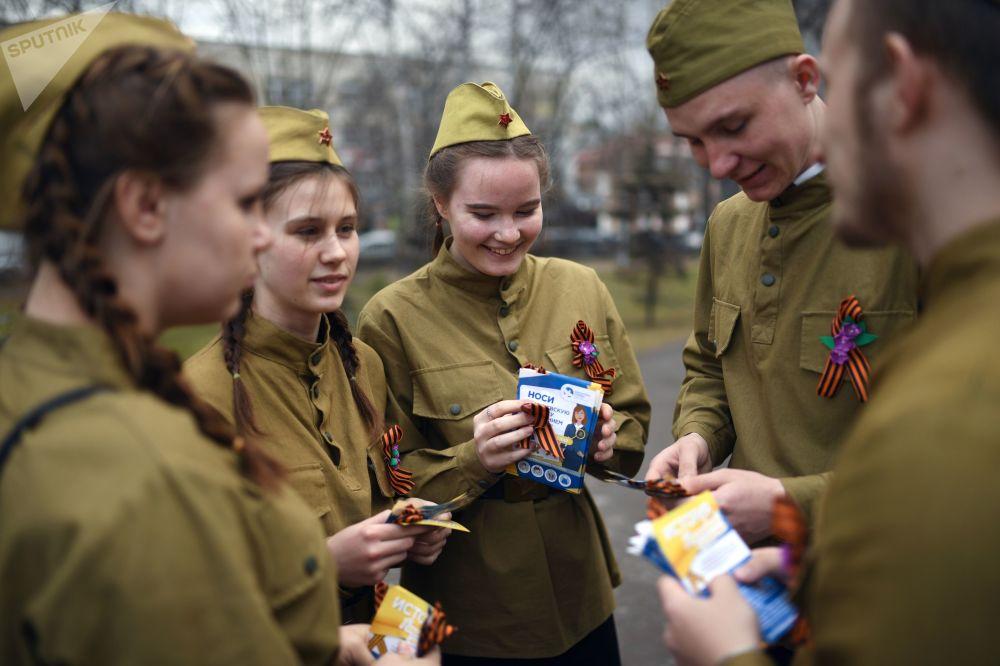 متطوعون يوزعون شرائط جاورجيوس في ساحة الأول من مايو في نوفوسيبيرسك في إطار الحملة السنوية شريط جاورجيوس قبيل عيد النصر