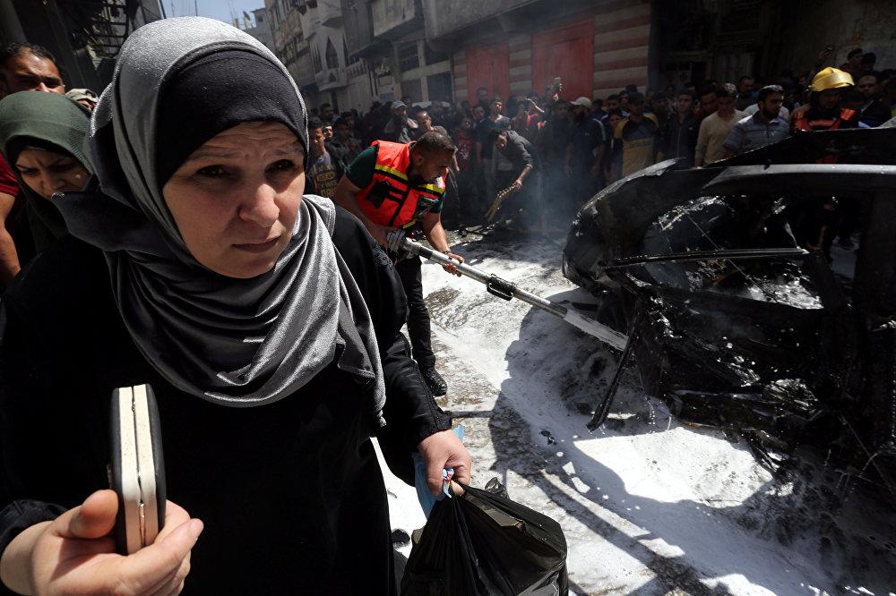 سيدة فلسطينية تمر في أثناء إخماد حريق في سيارة القيادي الحمساوي حامد أحمد عبد الخضري الذي قتل في غارة جوية إسرائيلية في مدينة غزة