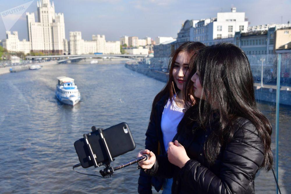 فتاتان تلتقطان صورة سيلفي على خلفية حديقة زارياديه في موسكو