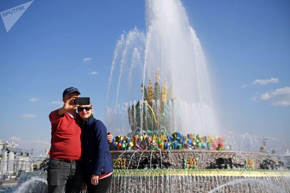 سياح يلتقطون صورة على خلفية نافورة كاميني تسيفتوك في حديقة في دي إن خا في موسكو