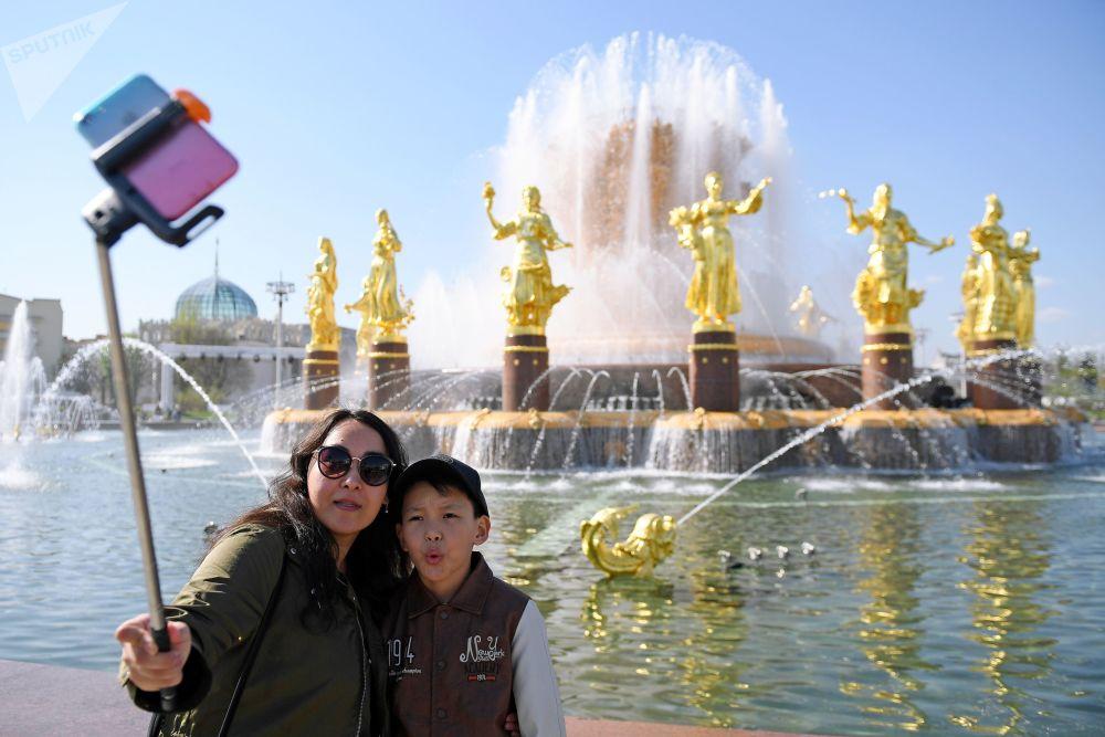 سياح يلتقطون صورة سيلفي على خلفية نافورة صداقة الشعوب في حديقة في دي إن خا في موسكو