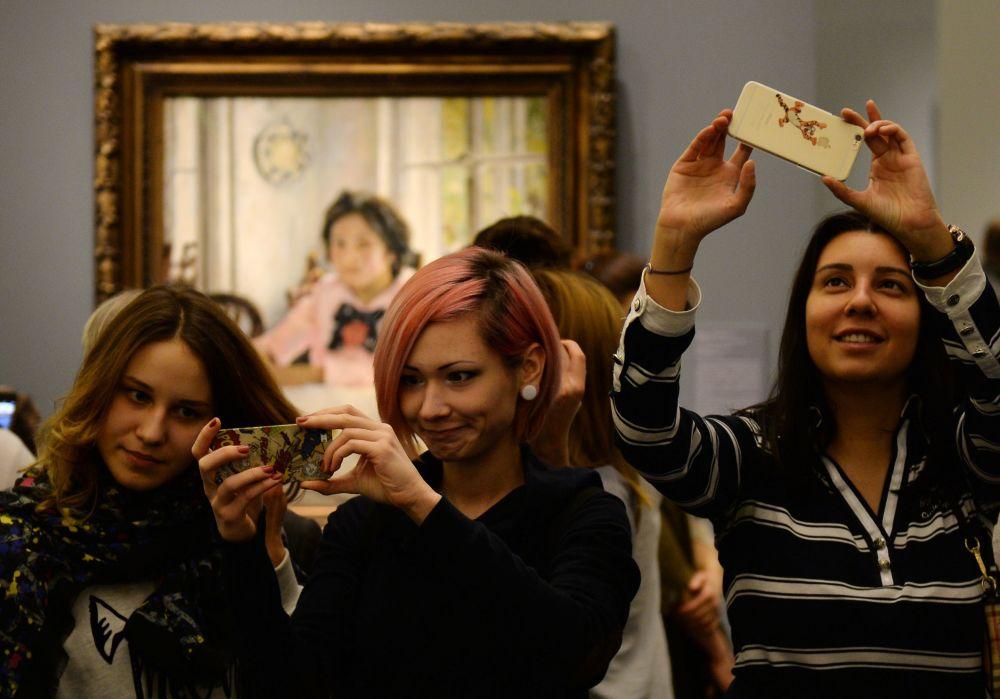 زوار متحف تريتياكوفسكايا غاليريا يلتقطون صور سيلفي على خلفية لوحة الفتاة والخوخ الشهيرة للرسام الروسي فالنتين سيروف، في موسكو