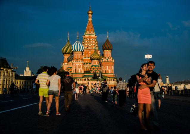 مواطنون وسياح يلتقطون صورة سيلفي على خلفية الساحة الحمراء في موسكو