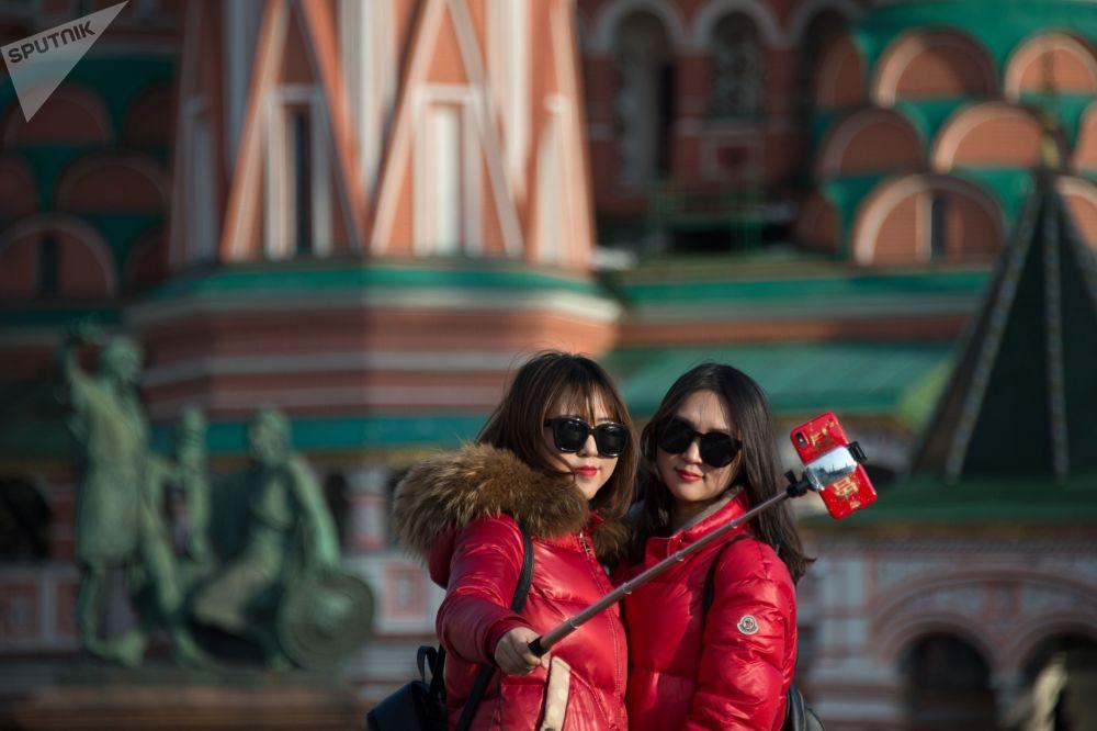 فتاتان تلتقطان صورة سيلفي على خلفية كتدرائية القديس باسل في موسكو