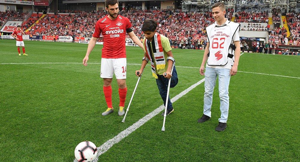 الفتى العراقي بطل صورة الرغبة في الحياة يركل كرة البداية في مباراة بالدوري الروسي