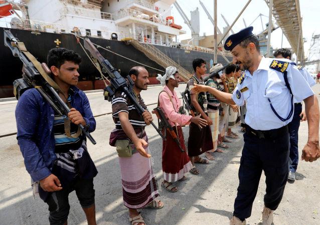 ضابط خفر السواحل اليمني يصافح الحوثيين أثناء مغادرتهم ميناء الصليف في محافظة الحديدة، 11 مايو/ أيار 2019