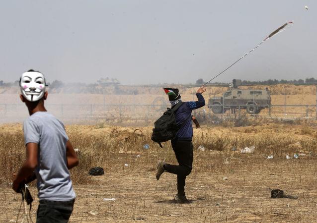 شباب فلسطينيون يقذفون الحجارة في شرق خان يونس، جنوب قطاع غزة، أثناء إحياء الذكرى الـ 71 للنكبة، 15 مايو/ أيار 2019