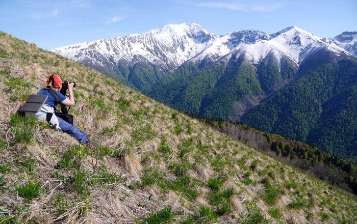 فتاة تلتقط صورا للجبال المغطاة بالثلوج في المحمية الطبيعية القوقازية باسم خ. غ. شابوشنيكوف