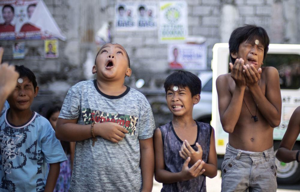 أولاد خلال مسابقة تحريك عملة معدنية من جبهة الرأس وصولا إلى الفم، في المهرجان السنوي على شرف القديسة ريتا كاشييسكايا في مانيلا، 19 مايو/ أيار 2019