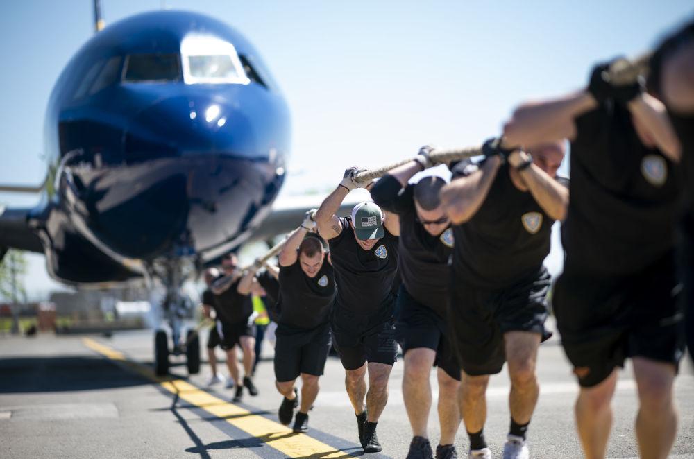 المشاركون في المسابقة السنوية Plane Pull لسحب طائرة من طراز جيت بليو أ320 (JetBlue A320) في مطار جون كينيدي الدولي في نيويورك، 21 مايو/ أيار 2019