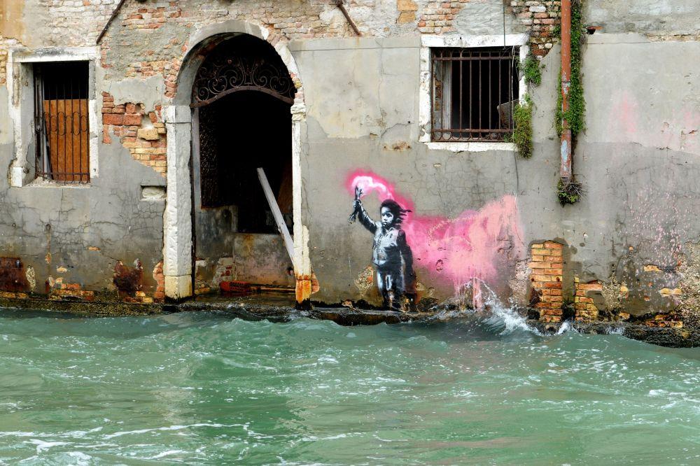 الرسام البريطاني بانكسي (Banksy) يرسم لاجئا بريطانيا على أحد جدران منزل يطل على القناة المائية ريو دي كا فوسكاري في مدينة فينيسيا (البندقية)،  إيطاليا 21 مايو/ أيار 2019
