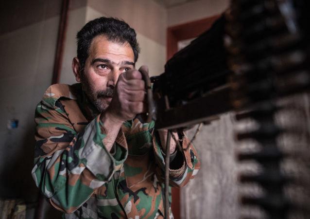 جندي سوري يراقب مدينة حمص