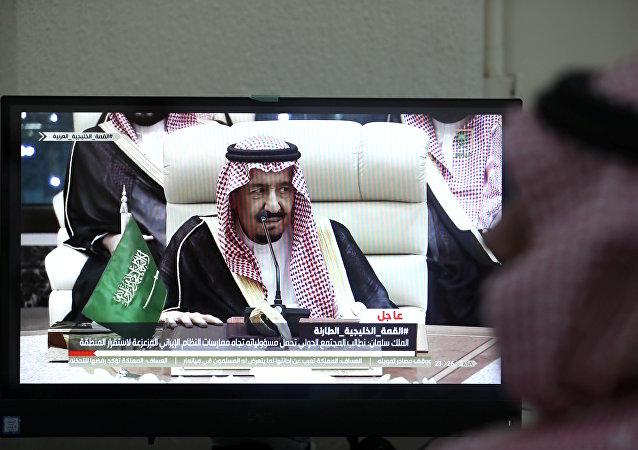صحفي يتابع خطاب العاهل السعودي الملك سلمان بن عبد العزيز على شاشة التلفزيون في المركز الإعلامي خلال القمة الإسلامية الرابعة عشرة في مكة، 30 مايو/أيار 2019