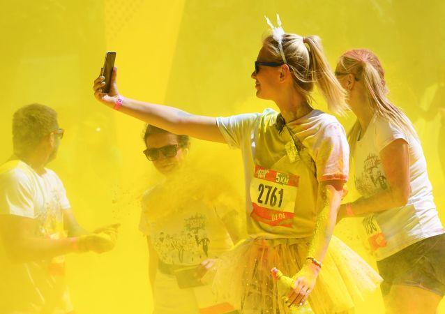 مشاركون يلقون مسحوقًا ملونًا أثناء احتفالهم بعد الانتهاء من سباق الألوان (Colour Run 2019) في ملعب لوجنيكي في موسكو، 2 يونيو/ حزيران 2019