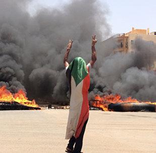 متظاهر سوداني يلوح بعلامة النصر بعد فض اعتصام المعارضة في السودان