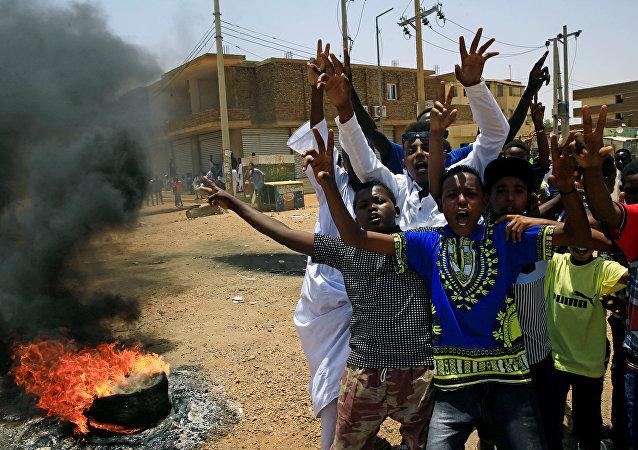 متظاهرون سودانيون يهتفون بشعارات عند أحد المتاريس مطالبين المجلس العسكري الانتقالي في البلاد بتسليم السلطة إلى المدنيين