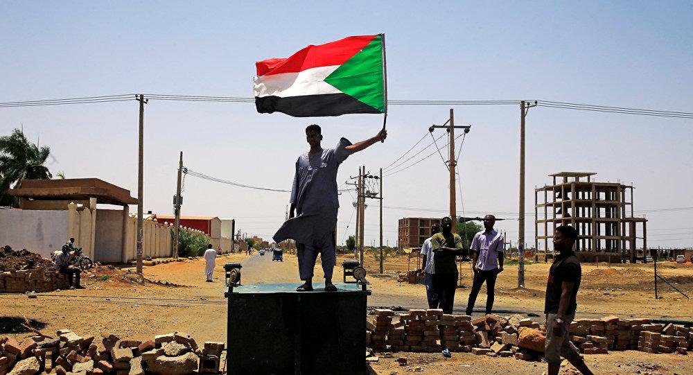 متظاهر سوداني يحمل راية وطنية وهو يقف على أحد المتاريس على طول شارع يطالب المجلس العسكري الانتقالي في البلاد بتسليم السلطة إلى المدنيين
