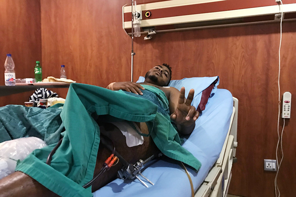مصاب بعيار ناري في الحملة على المتظاهرين السودانيين يلوح بعلامة النصر داخل وهو يتلقى العلاج في مستشفى بالخرطوم