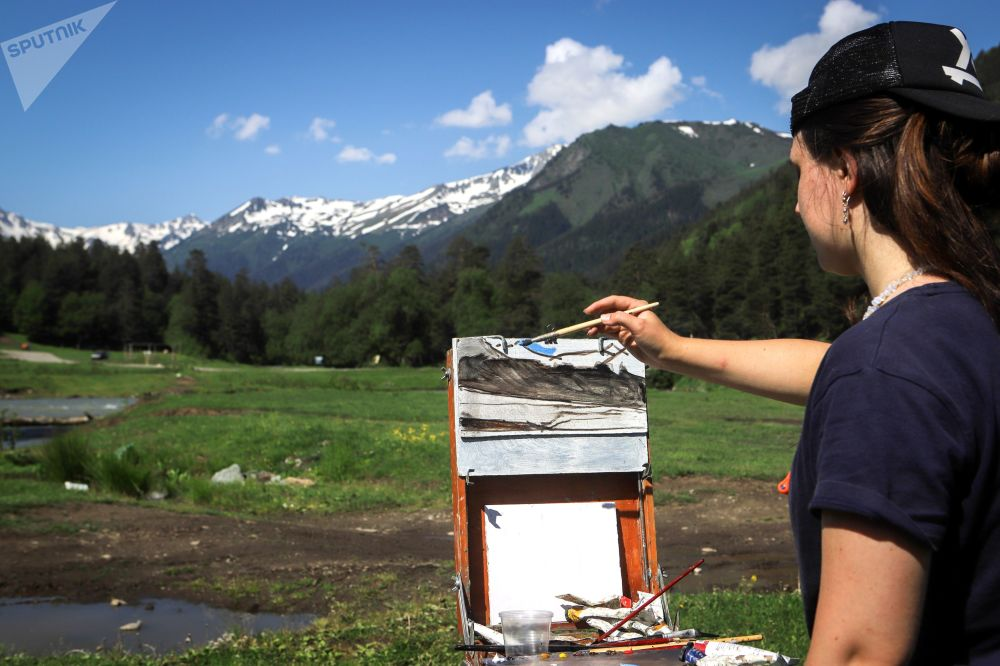 فنانة ترسم منظر طبيعي في أراضي وادي صوفيا في جمهورية كراتشاي - تشركيسيا