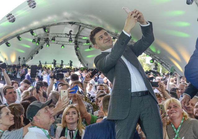 رئيس أوكرانيا فلاديمير زيلينسكي يأخذ صورة سيلفي في المؤتمر الأول لحزبه خادم الشعب في الحديقة النباتية بمدينة كييف، أوكرانيا 9 يونيو/ حزيران 2019