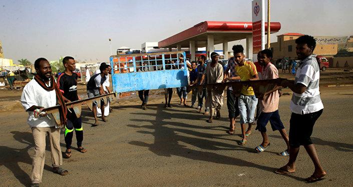 متظاهرون سودانيون يقيمون حاجزًا في أحد الشوارع ويطالبون المجلس العسكري الانتقالي في البلاد بتسليم السلطة إلى المدنيين