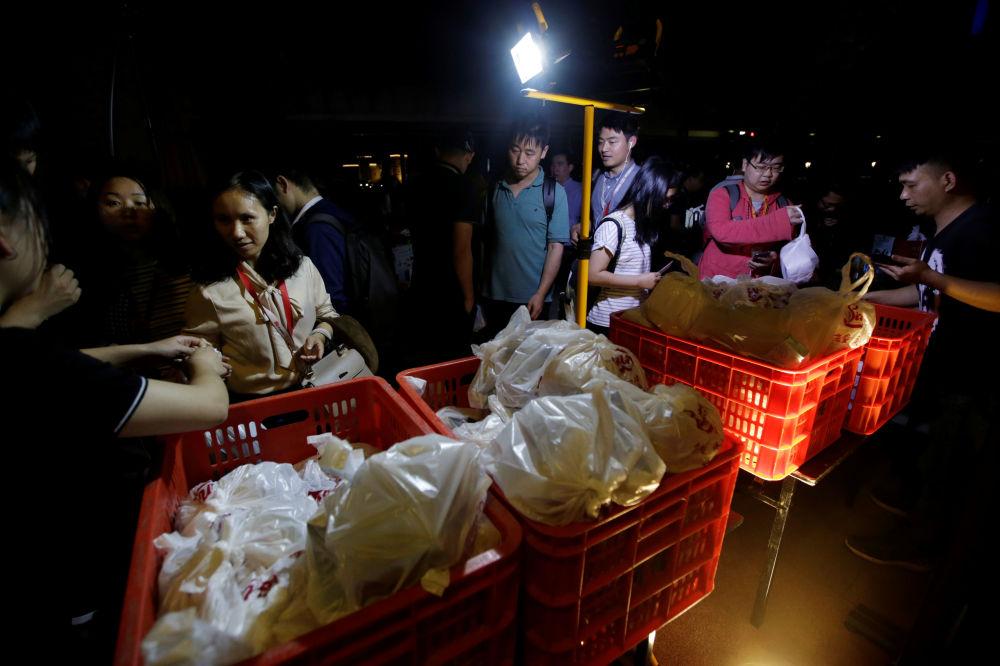 موظفو شركة هواوي لدى توزيع وجبات العشاء المجانية للموظفين الذين اشتغلوا ساعات إضافية (أوفر تايم) خلال اليوم، في الحرم الجديد لـ هواوي سونغشان ليك نيو كامبوس (Huawei Songshan Lake New Campus)، 30 مايو/ أيار 2019