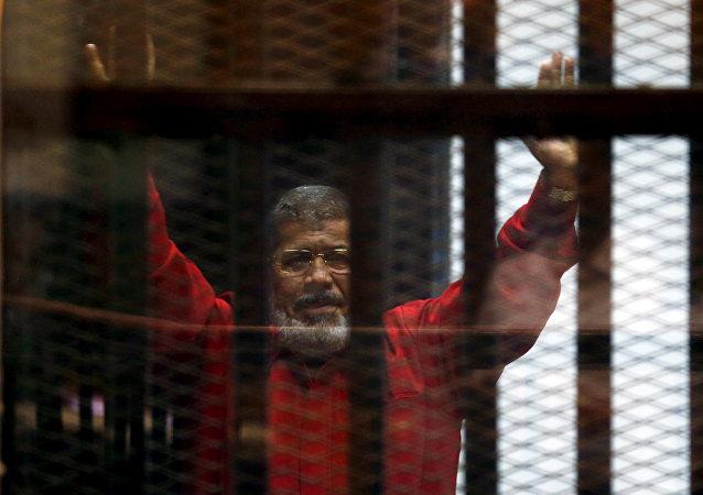 الرئيس المصري المعزول محمد مرسي يحيي محاميه وأفراد أسرته من وراء القضبان في محكمة ويرتدي الزي الأحمر لسجين حكم عليه بالإعدام