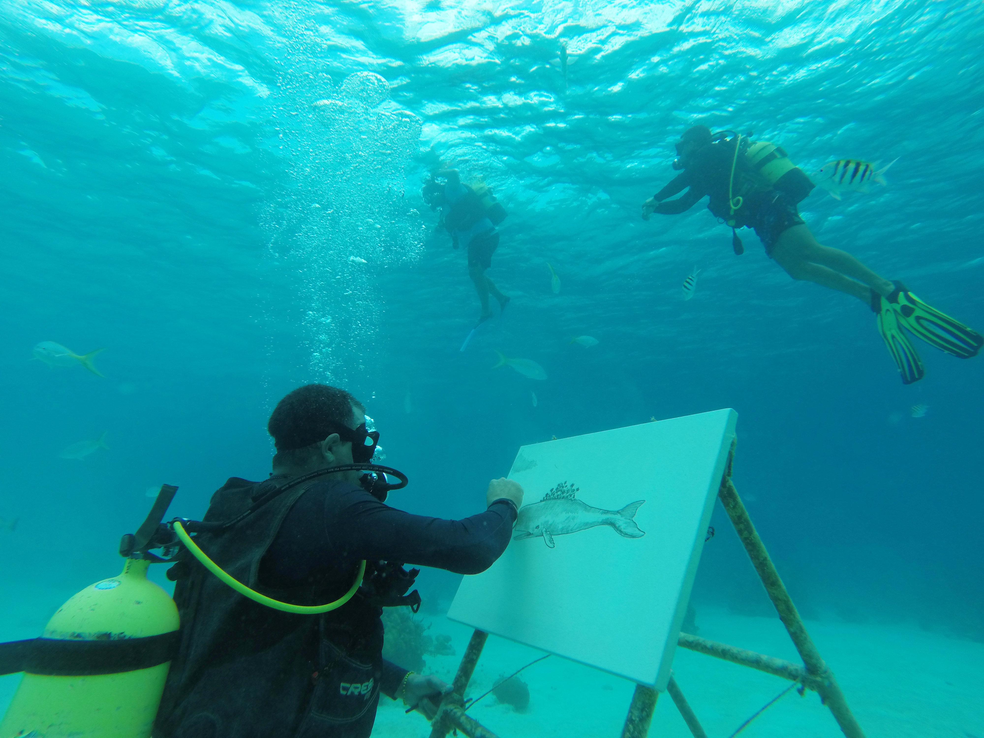 لفنان الكوبي ساندور غونزاليس يتحدث إلى وسائل الإعلام بعد رسمه تحت الماء في بونتا بيرديز