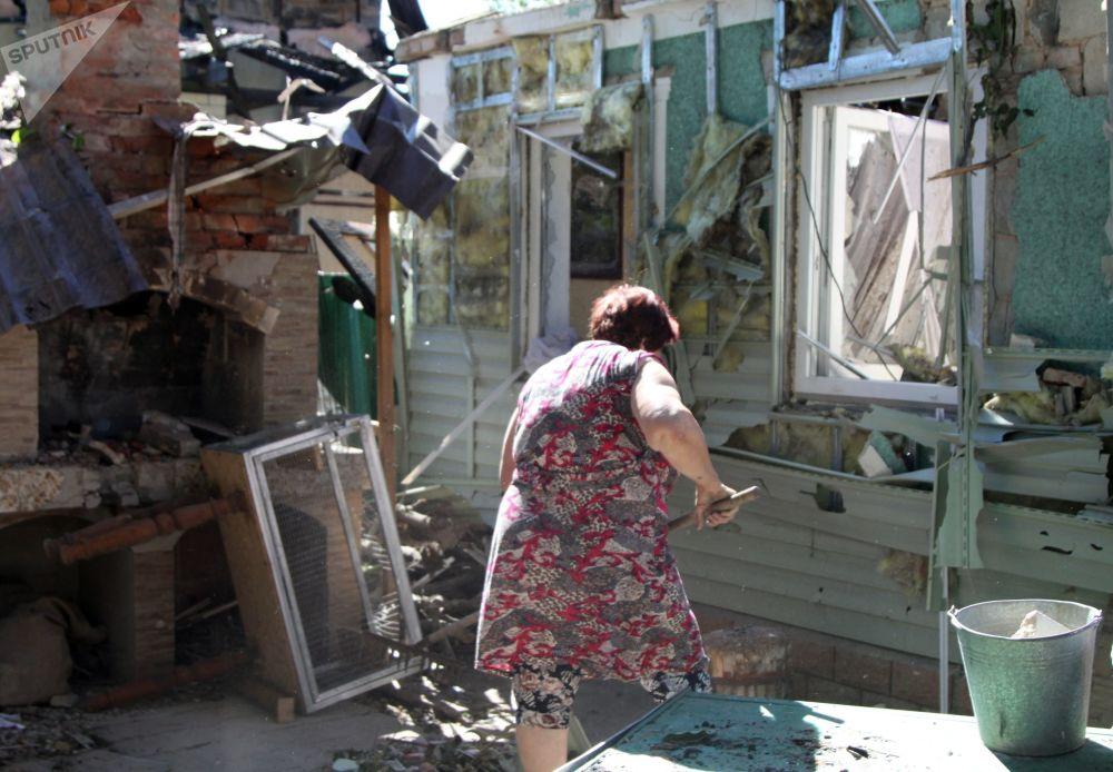 امرأة تنظف القمامة في ساحة مبنى سكني في دونيتسك، الذي تضرر من القصف