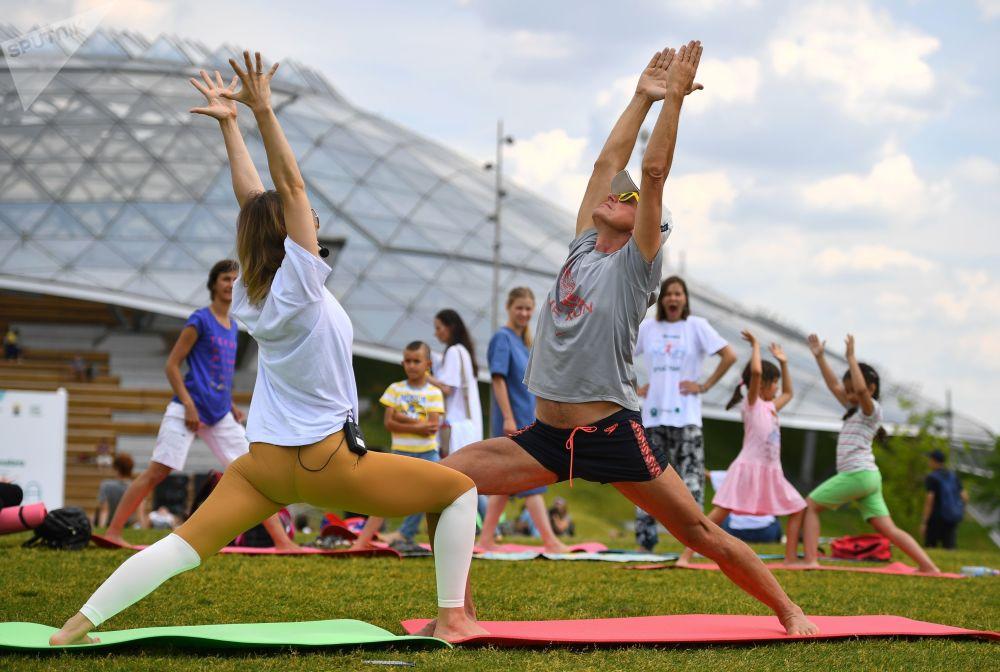 المشاركون في مشروع 365 خلال المهرجان الدولي الخامس لليوغا في حديقة زارياديه في موسكو
