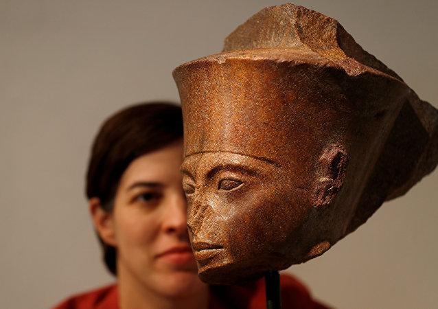 لايتيتيا ديلالوي رئيس قسم الآثار في كريستيز تلتقط صورة فوتوغرافية مع رأس توت عنخ آمون قبل بيعها في دار كريستيز للمزادات في لندن