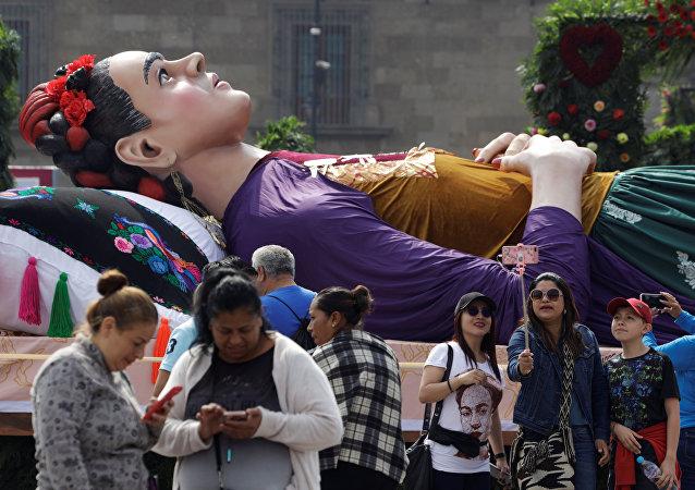 يلتقط الناس الصور بجوار تمثال كبير للفنانة المكسيكية فريدا كالو ملقاة على سرير خلال معرض لوس كولورز دي فريدا كالو في ميدان زوكالو في مكسيكو سيتي