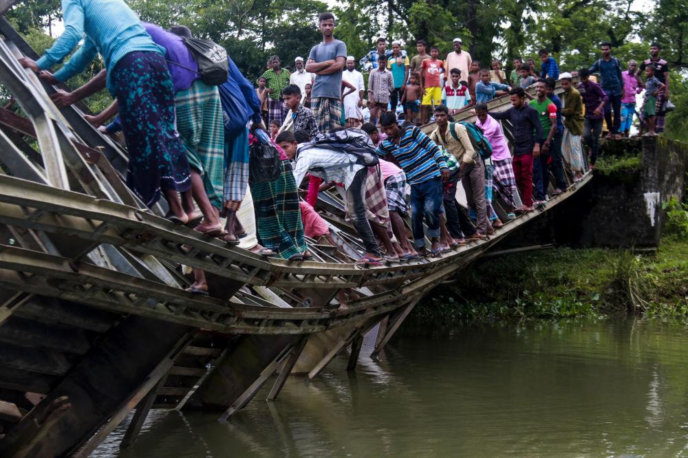 مارة على جسر مكسور في سيلهيت، بنغلاديش 7 يوليو/ تموز 2019