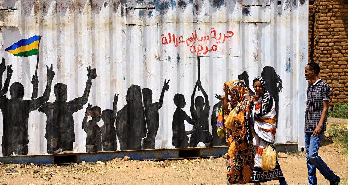مدنيون يعبرون أمام كتابة على الجدران باللغة العربية الحرية والسلام والعدالة والمدنية في منطقة بري بالخرطوم