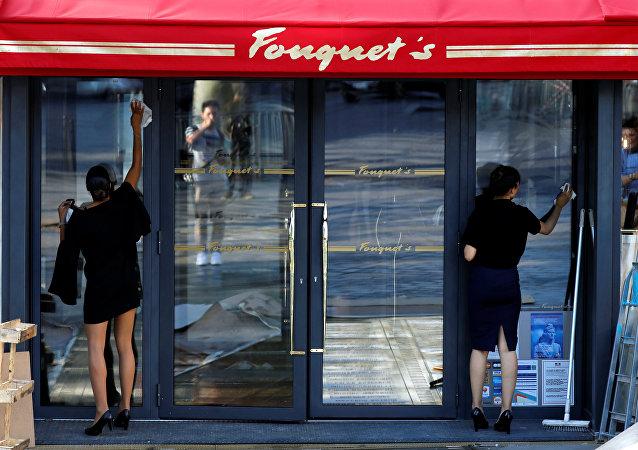 موظفون يقومون بتنظيف نوافذ مطعم فوكيه عشية إعادة افتتاحه في الشانزليزيه بعد حوالي 4 أشهر من نهبه من قبل السترات صفراء