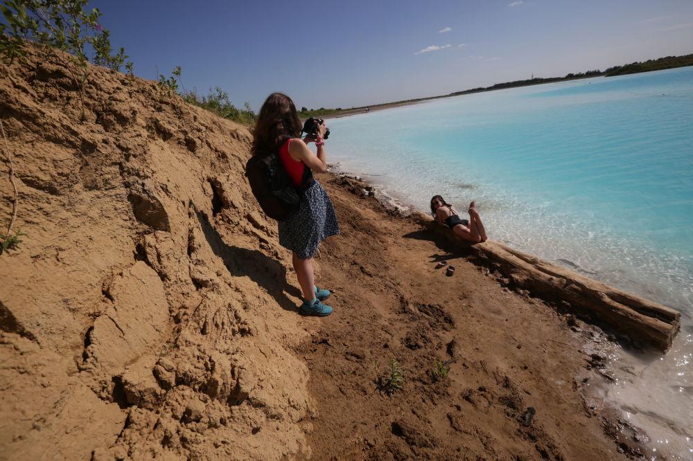فتيات يلتقطن صورا على خلفية البحيرة القرمزية، التي أطلق عليها أهالي المنطقة المحليون بـ جزر المالديف، 11 يوليو/ تموز 2019